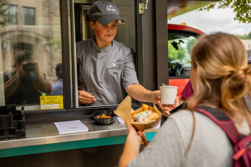 Molly, a Culinary camper serves food from one of the food trucks to a customer.