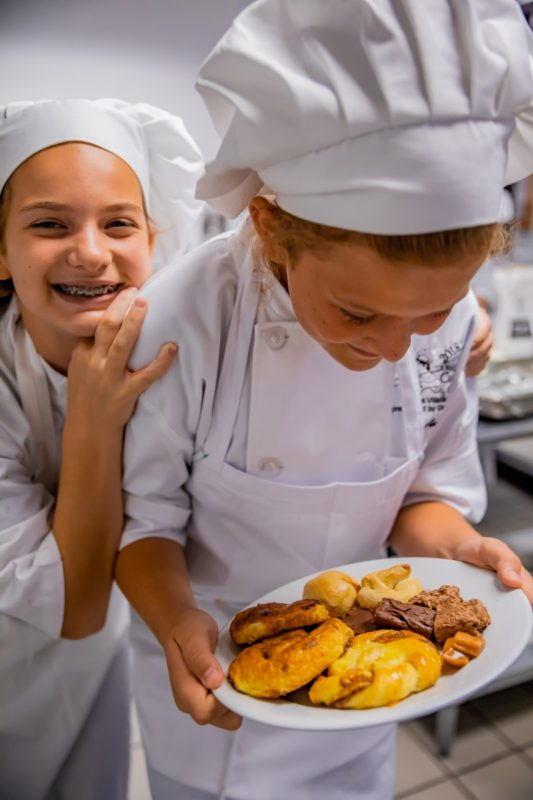 Two culinary campers smile and show off what they learned how to bake in a culinary camp class.